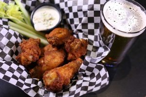basket of crispy wings with celery sticks, bleu cheese dressing and a glass of dark beer